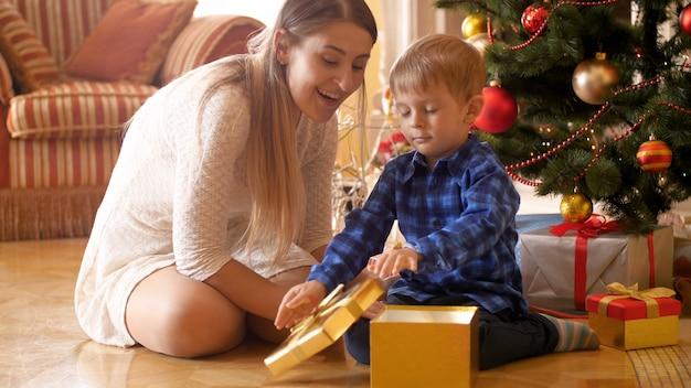 4 filmati di k del ragazzino sorridente felice che apre la sua confezione regalo a natale e che mostra il regalo a sua madre. famiglia dare e ricevere regali durante le vacanze invernali e le celebrazioni.