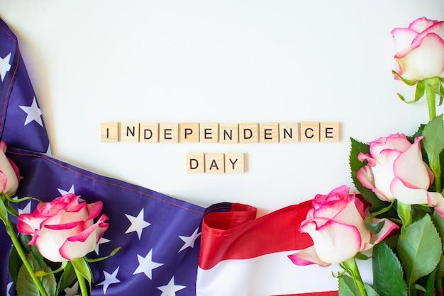 4 luglio stati uniti. bandiera americana e rose lettere in legno con testo giorno dell'indipendenza per il giorno della memoria