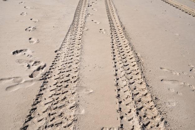 Tracce di pneumatici 4x4 che si incrociano tracce di pneumatici sullo sfondo di texture di sabbia.