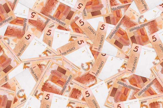 5 banconote in rubli bielorussi si trovano in un grande mucchio. grande quantità di denaro