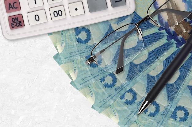 5 dollari canadesi fatture ventilatore e calcolatrice con occhiali e penna