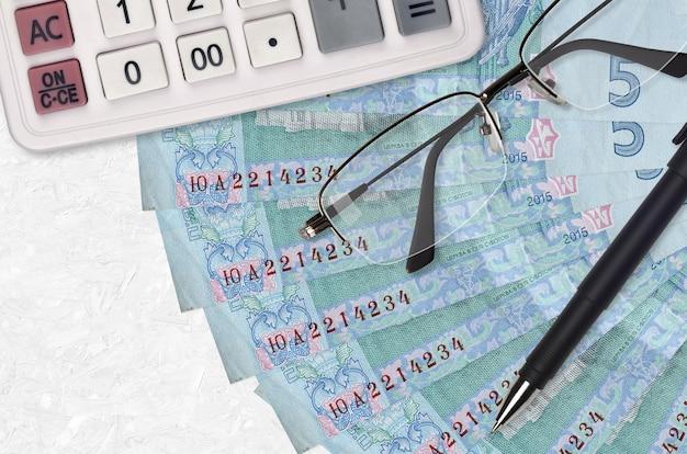 5 grivnie ucraine fatturano ventaglio e calcolatrice con occhiali e penna. prestito aziendale o concetto di stagione di pagamento delle tasse. progetto finanziario