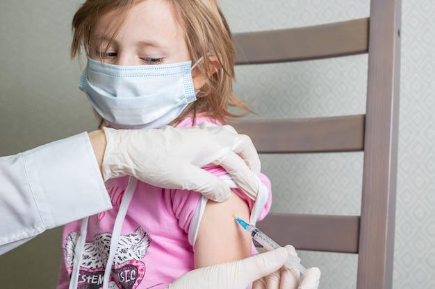 Una bambina caucasica di 5 anni con una mascherina medica riceve un vaccino, che fa capolino con gli occhi bassi sulla siringa
