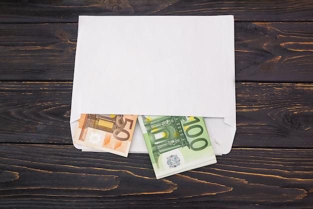 Fatture da 50 e 100 euro in una busta bianca su uno sfondo di legno. vista dall'alto. un sacco di soldi in una busta.