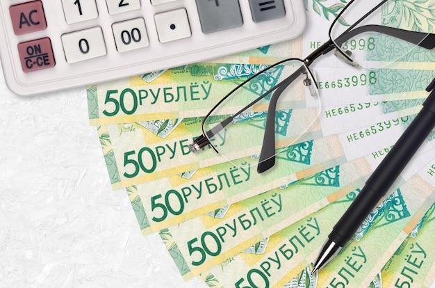 Ventaglio da 50 rubli bielorussi e calcolatrice con occhiali e penna. prestito aziendale o concetto di stagione di pagamento delle tasse. progetto finanziario