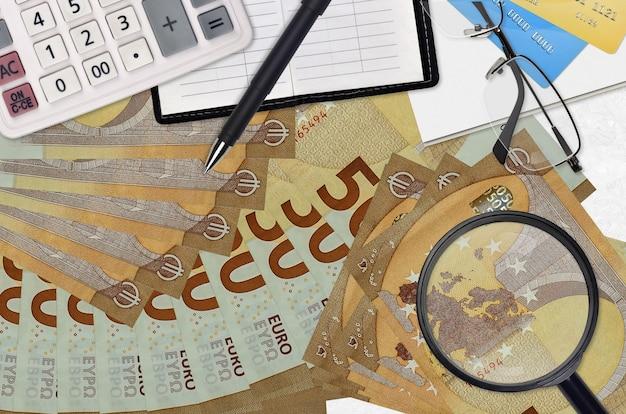 Banconote da 50 euro e calcolatrice con occhiali e penna. concetto di stagione di pagamento delle tasse o soluzioni di investimento. alla ricerca di un lavoro con guadagni salariali elevati