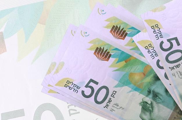 50 nuove banconote in sicli israeliani si trovano in pila sullo sfondo di una grande banconota semitrasparente
