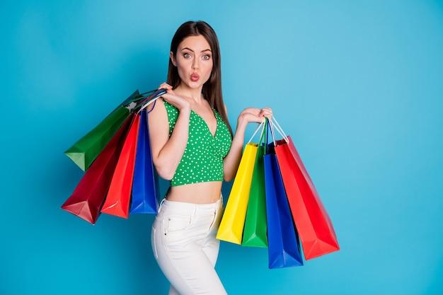 50% di vendite. la ragazza stupita fa le labbra carnose imbronciate e tiene molte borse impressionate indossa pantaloni bianchi pantaloni canotta isolata su sfondo di colore blu