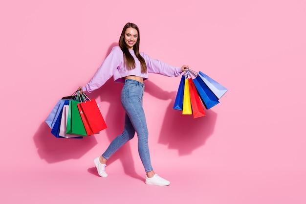 50% di vendite, foto laterale del profilo completo del corpo di una ragazza allegra positiva andare a piedi tenere molte borse indossare maglione viola lilla stile elegante maglione alla moda jeans denim isolato sfondo di colore pastello