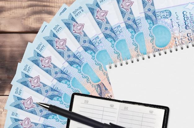 Ventaglio di banconote da 50 rupie dello sri lanka e blocco note con rubrica e penna nera. concetto di pianificazione finanziaria e strategia aziendale