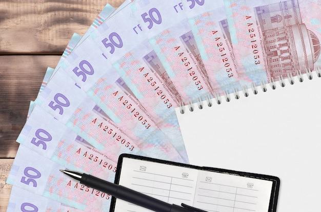 Ventaglio da 50 grivnie ucraine con blocco note e rubrica e penna nera. concetto di pianificazione finanziaria e strategia aziendale