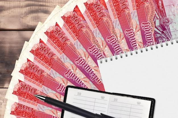 Ventaglio da 500 banconote riel cambogiano e blocco note con rubrica e penna nera. concetto di pianificazione finanziaria e strategia aziendale. contabilità e investimenti