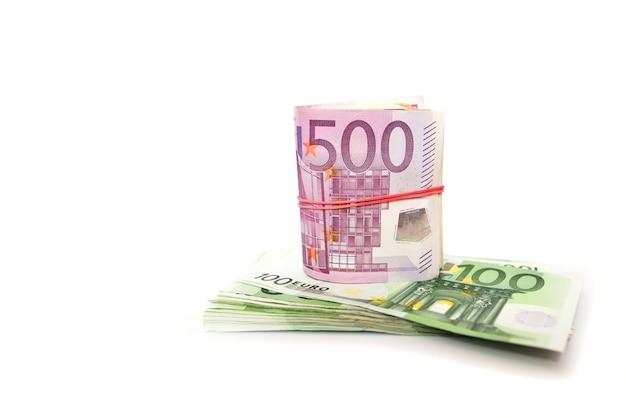 500 euro legati con un elastico e una pila di 100 euro su una superficie bianca. copia spazio.