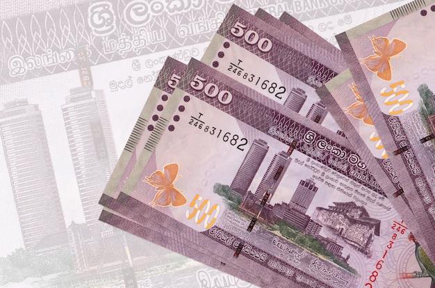 Banconote da 500 rupie dello sri lanka si trovano in pila sullo sfondo di una grande banconota semitrasparente.