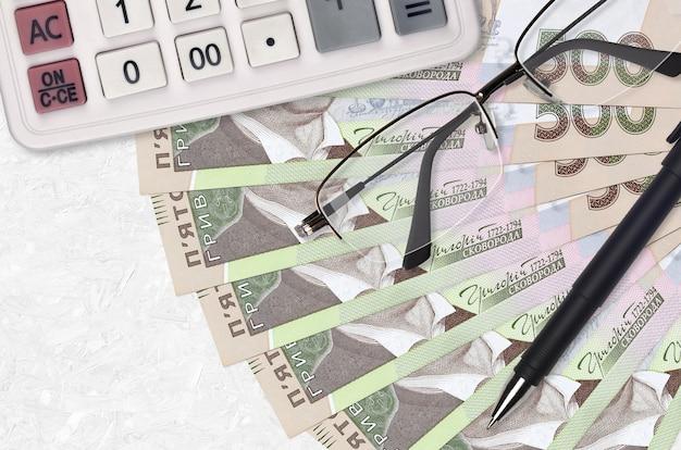 500 grivnie ucraine fatture ventilatore e calcolatrice con occhiali e penna. prestito aziendale o concetto di stagione di pagamento delle tasse. progetto finanziario