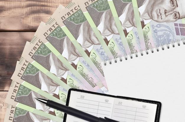 Ventaglio di banconote da 500 grivnie ucraine e blocco note con rubrica e penna nera