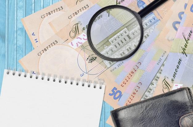 500 banconote hryvnia ucraine e lente d'ingrandimento con borsa nera e blocco note