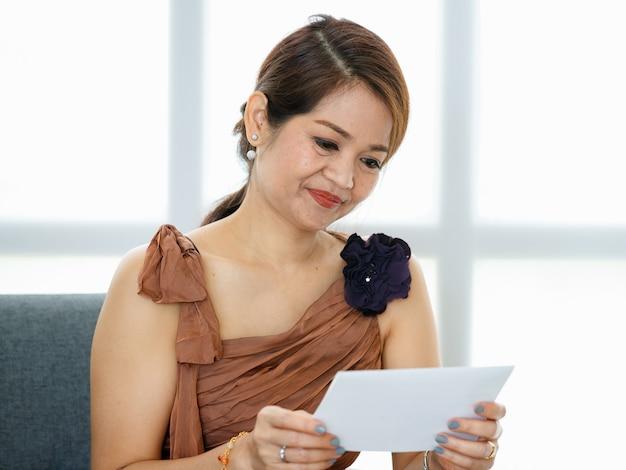 Anni '50 asiatica ricca di lusso senior smiley donna seduta sul divano nella stanza interna, ben vestita, indossando accessori eleganti, tenendo e leggendo la carta in mano.