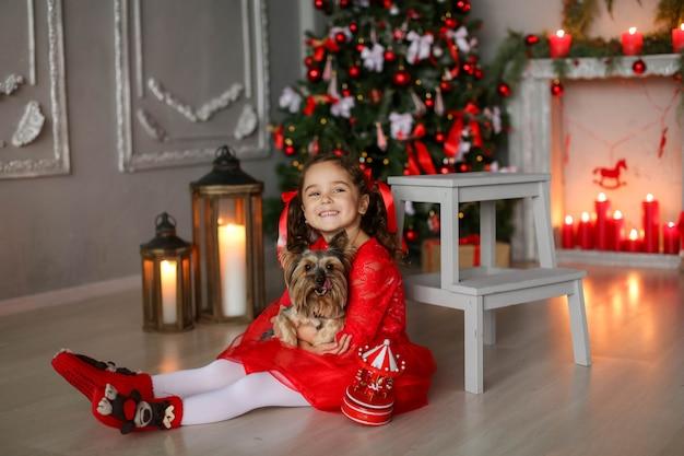 La bambina di 6-7 anni nella notte di natale abbraccia il suo amato animale domestico.