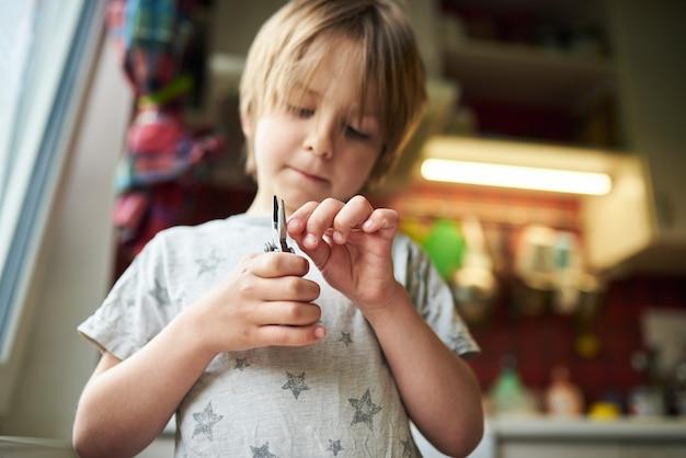 Il ragazzo di 6 anni crea artigianato a casa. tiene in mano una pinza e un bastone di legno