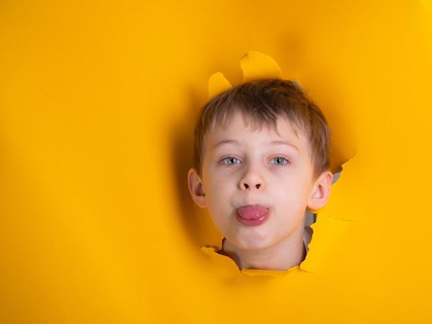 Un bambino di 6 anni mostra la sua lingua su uno sfondo giallo