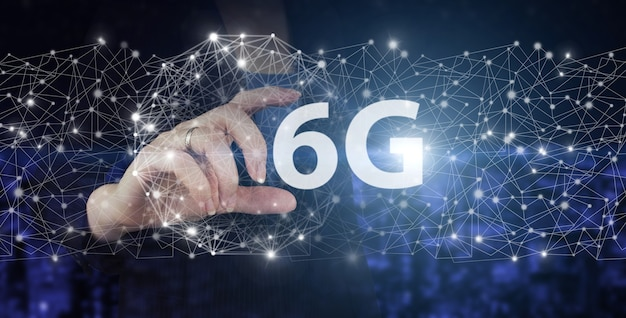 Componenti della tecnologia di comunicazione dei sistemi 6g. tenere in mano il segno dell'ologramma digitale 6g su sfondo sfocato scuro della città. sistemi wireless e internet delle cose iot.