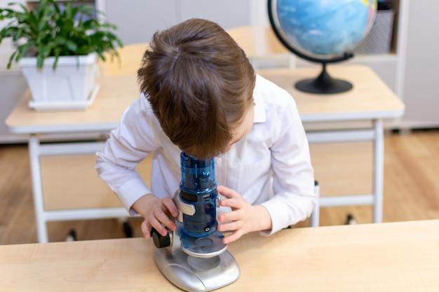 Un bambino di 7-8 anni in camicia bianca guarda al microscopio. foto di alta qualità