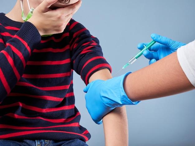Ragazzo di 7 anni vaccinato, che indossa una mascherina chirurgica isolata su grigio, concetto di vaccinazione