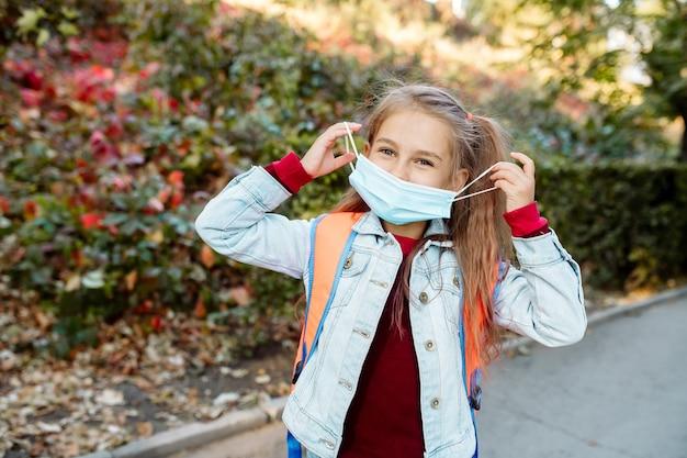 Una bambina di 7 anni con maschera facciale va a scuola lungo un vicolo del parco in autunno