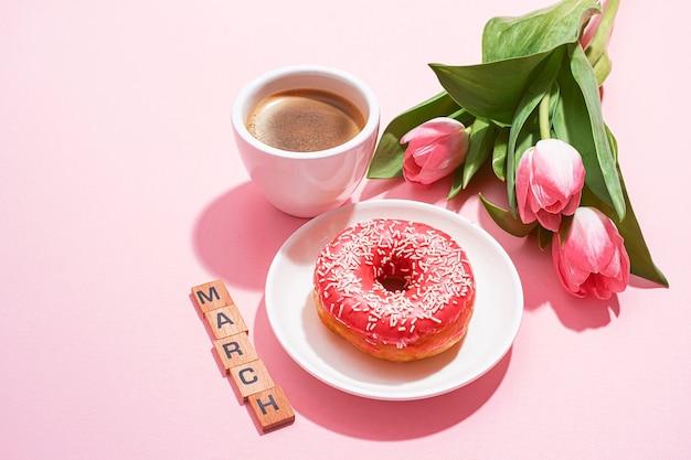 Biglietto di auguri dell'8 marzo con una tazza di caffè e un piattino con una ciambella che forma il numero otto e un tenero tulipano rosa nelle vicinanze