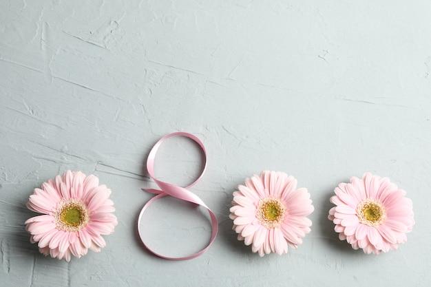 8 marzo, giornata internazionale della donna. figura otto di nastro rosa con bellissimi fiori di gerbera su grigio. spazio per il testo