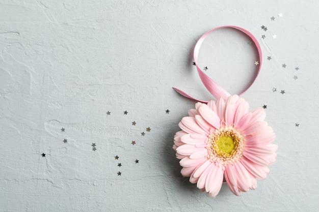 8 marzo, giornata internazionale della donna. figura otto di nastro rosa con bella gerbera su grigio. spazio per il testo
