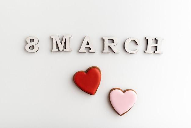 8 marzo scritte e biscotti a forma di cuore rosa e rossi su fondo bianco. festa della donna.