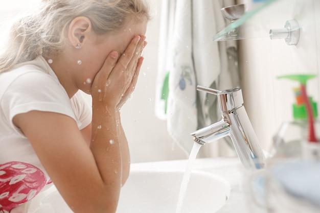 Bambina di 8 anni si lava la faccia in bagno al mattino.