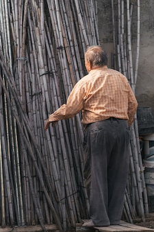 Uomo di 82 anni che prepara i materiali per costruire la struttura in fattoria