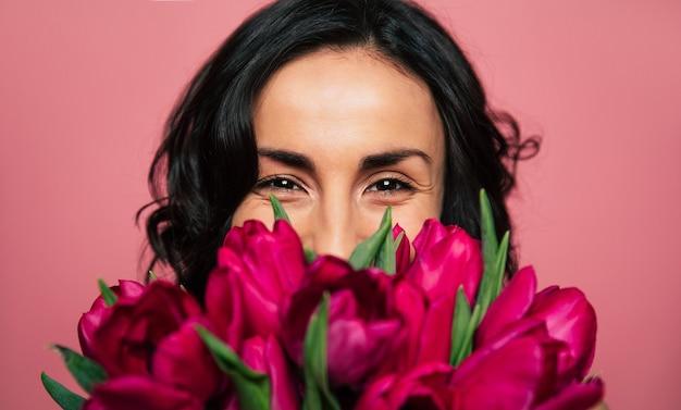L'8 marzo. foto ravvicinata di un'allegra donna bruna, che guarda nella telecamera e nasconde una parte del viso sopra il mazzo di tulipani.