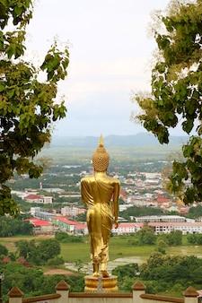 L'immagine del buddha d'oro alta 9 metri nella postura a piedi del wat phra that khao noi, un tempio sulla collina nella provincia di nan, thailandia