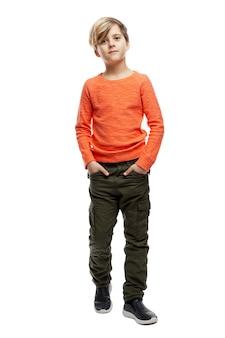 Un bambino di 9 anni con un maglione arancione e pantaloni verdi è in piedi con le mani in tasca.