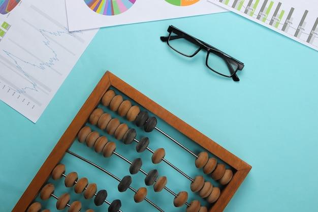Abaco con grafici e tabelle, bicchieri su pastello blu.