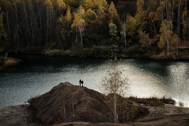 Miniera di carbone abbandonata, colline di sabbia marrone. miniere di produzione di rifiuti. paesaggio industriale in autunno con betulle gialle contro un cielo grigio.