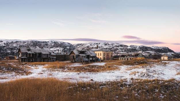 Case abbandonate contro il cielo artico. vecchio villaggio autentico di teriberka. penisola di kola. russia. vista panoramica.