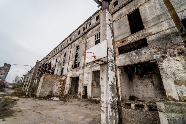 Vecchia fabbrica abbandonata che costruisce fuori. scarta la vecchia fabbrica industriale esteriore con le costruzioni