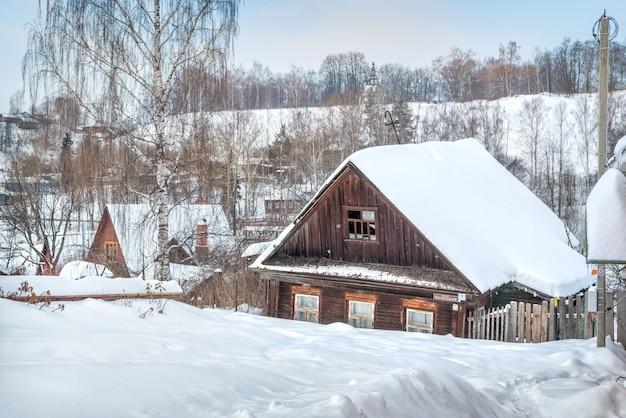 Vecchia casa in legno nera abbandonata a plyos alla luce di una giornata invernale sotto un cielo blu