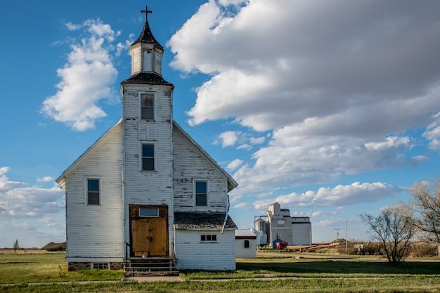 La chiesa unita di platone abbandonata con l'elevatore del grano di platone a platone, saskatchewan, canada