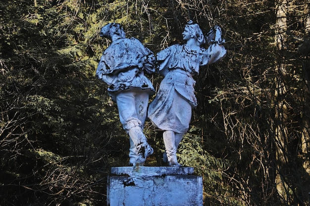 Statua abbandonata di un popolo che balla nella foresta
