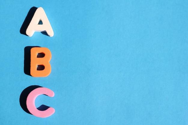 Prime lettere abc dell'alfabeto inglese su sfondo blu. copia spazio.
