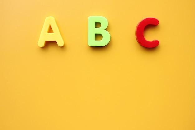 Prime lettere abc dell'alfabeto inglese su sfondo giallo. copia spazio.