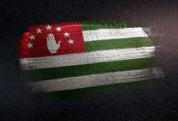 Bandiera dell'abkhazia fatta di vernice spazzola metallica sulla parete scura del grunge
