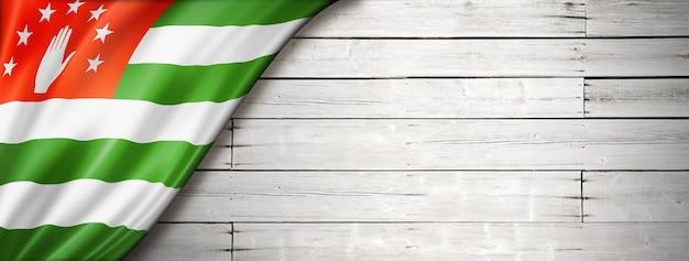 Bandiera dell'abkhazia sul vecchio muro bianco. banner panoramico orizzontale.