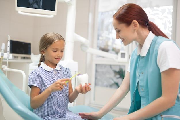 A proposito di cure odontoiatriche. medico professionista dai capelli rossi che racconta alla ragazza l'importanza delle cure dentistiche
